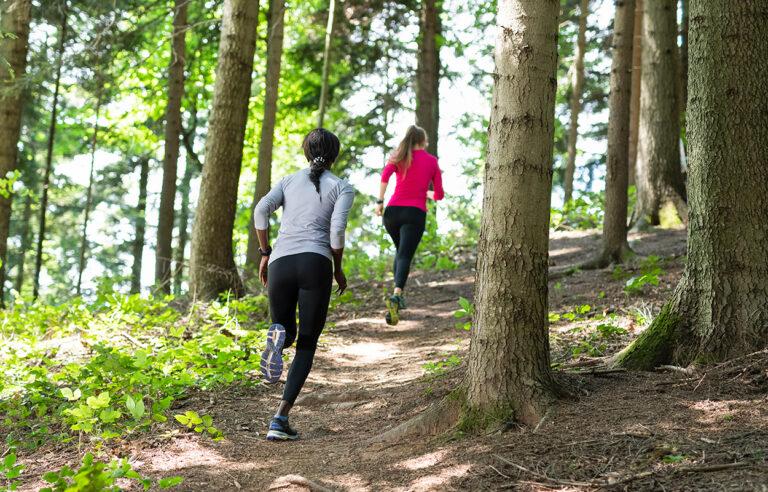 Polkujuoksu: Kaksi naista polkujuoksemassa metsässä