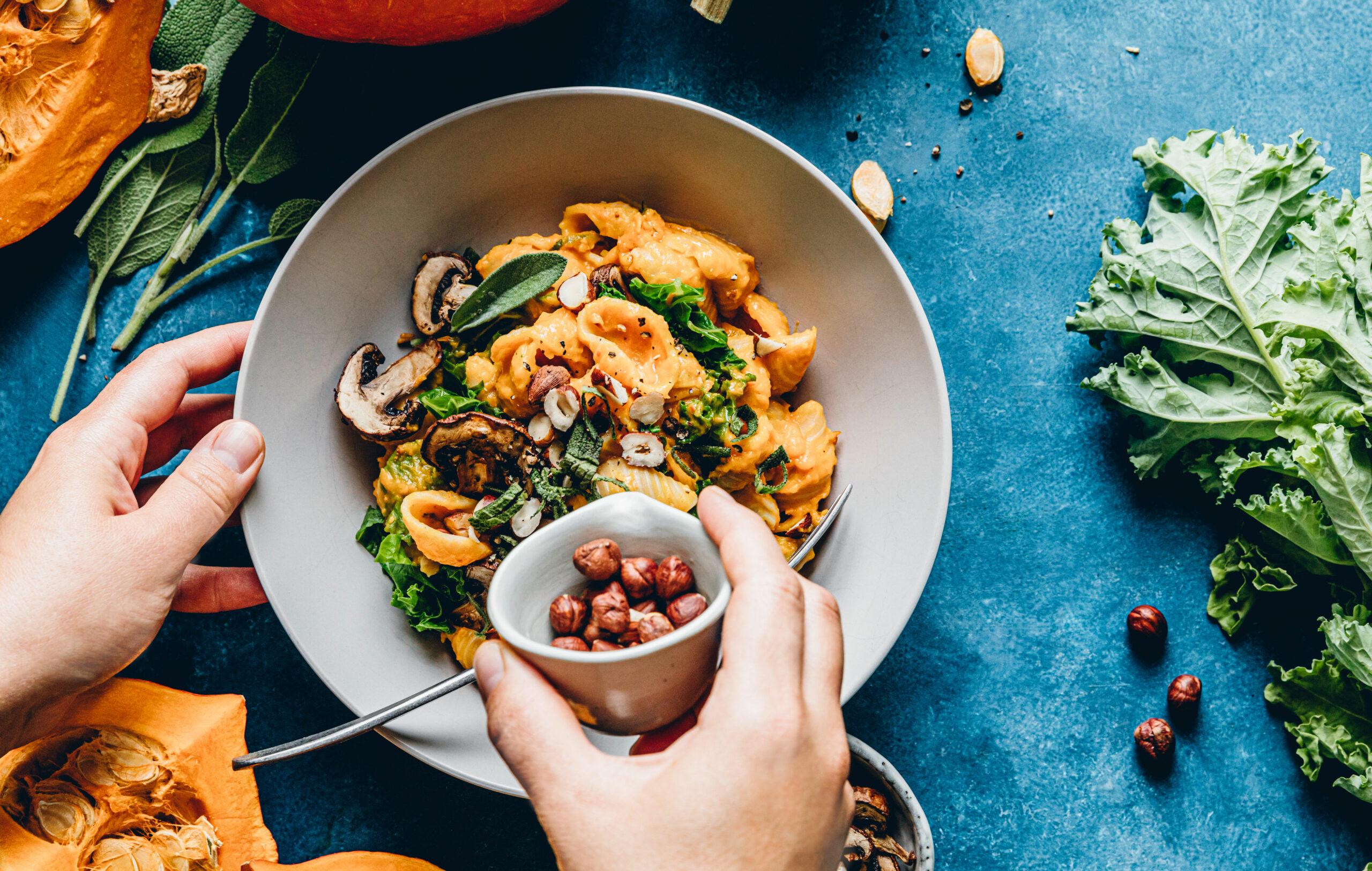 Oikea ruokarytmi – kädet asettelevat pähkinöitä värikkään ruokalautasellisen päälle.