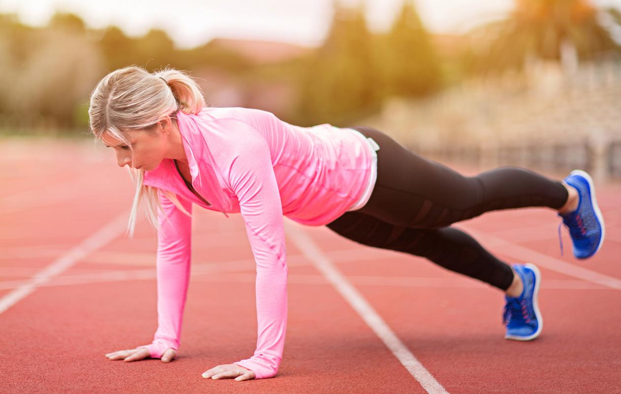 Nainen lankku-asennossa treenaamassa.