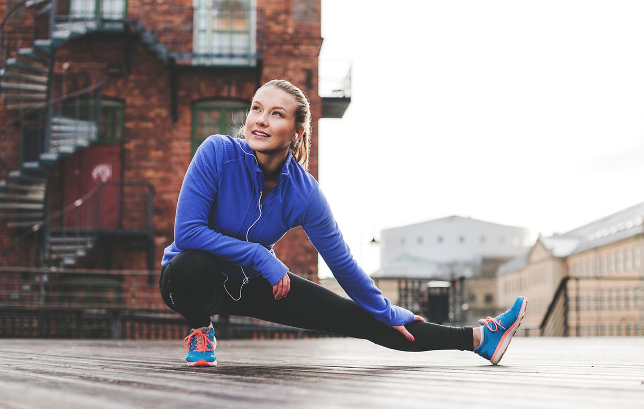Juoksukunto: nainen venyttää jalkaansa.