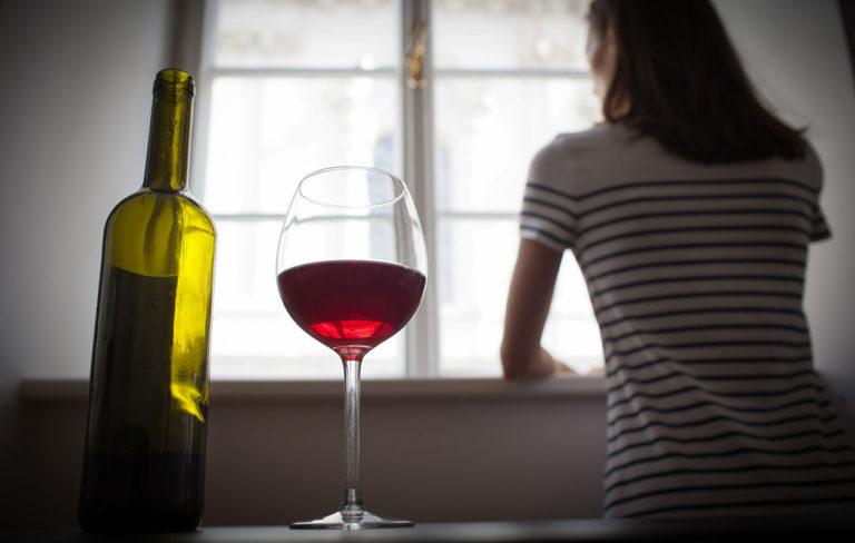 Nainen juomassa alkoholia yksin