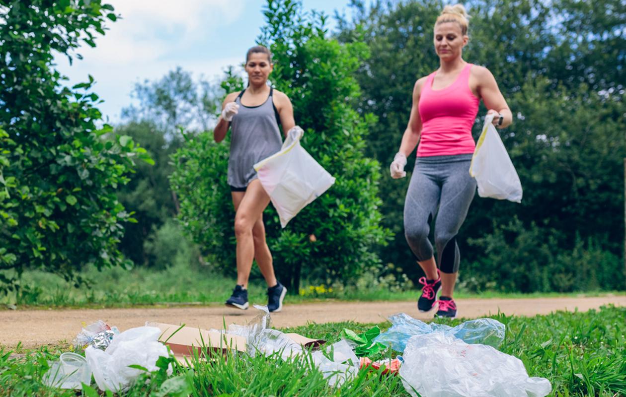 Plogging eli roskajuoksu: kaksi naista juoksee roskapussit käsissään.