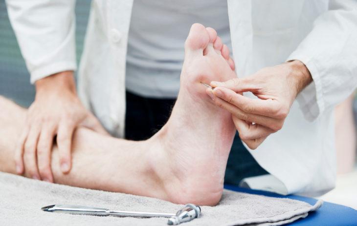 Diabetes: lääkäri tutkii jalkojen tuntoa.