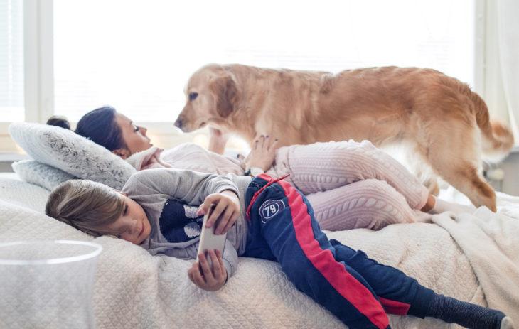 Köyhyysrajalla eläminen: Joa, Emma ja Dara-koira lepäilevät olohuoneen sängyllä.