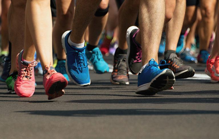 Ihmisillä jaloissa juoksukenkiä.