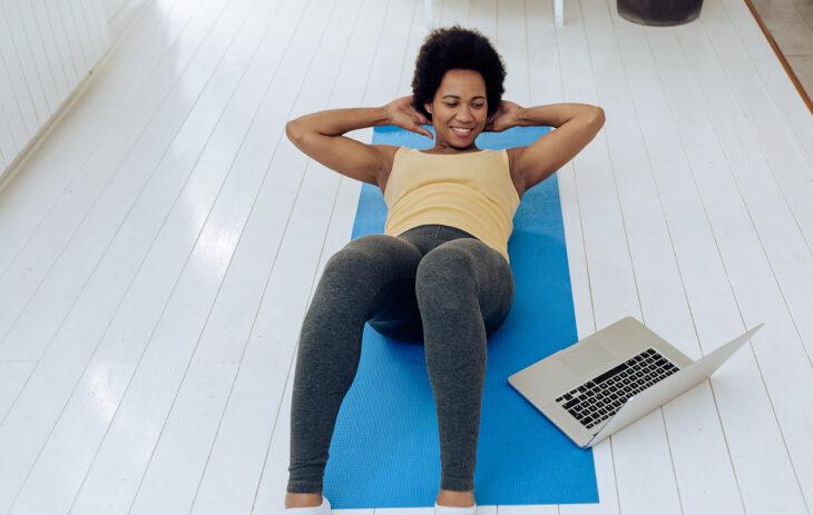 Tabata-treeni pitää sisällään erilaisia kuntoiluliikkeitä. Nainen tekee vastaslihasliikettä lattialla.
