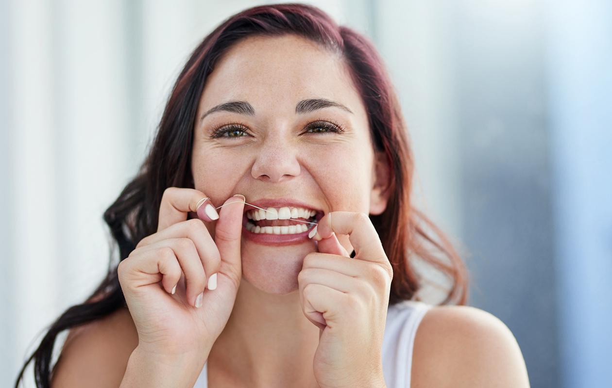 Nainen käyttää hammaslankaa.