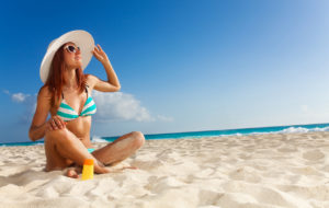 Nainen istuu aurinkoisella uimarannalla.