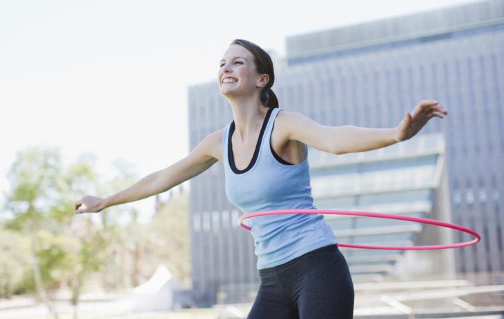Nainen pyörittää hulavannetta. Hulavanne on hauskaa treeniä!