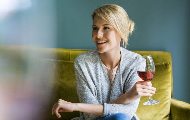 Nainen istuu sohvalla viinilasi kädessään. Alkoholista luopuminen kannattaa – listasimme 9 huomattavaa hyötyä.