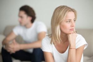 Nainen istuu ja katsoo poispäin miehestä.