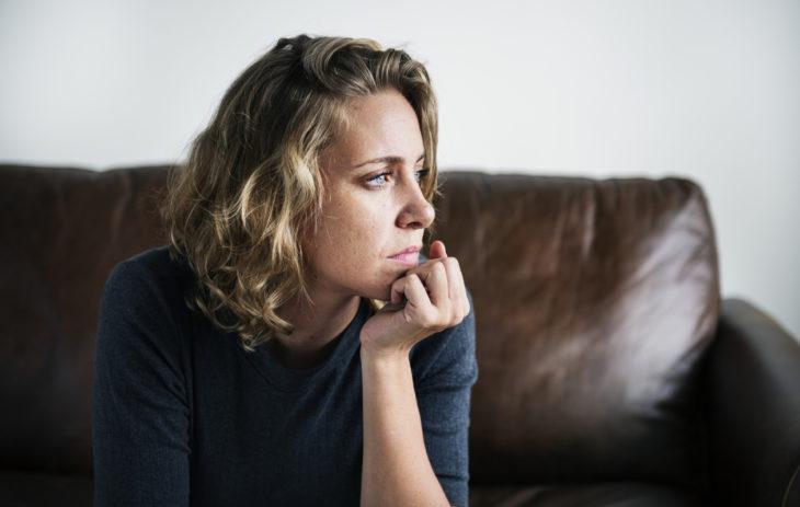 Nainen istuu sohvalla surullisena.