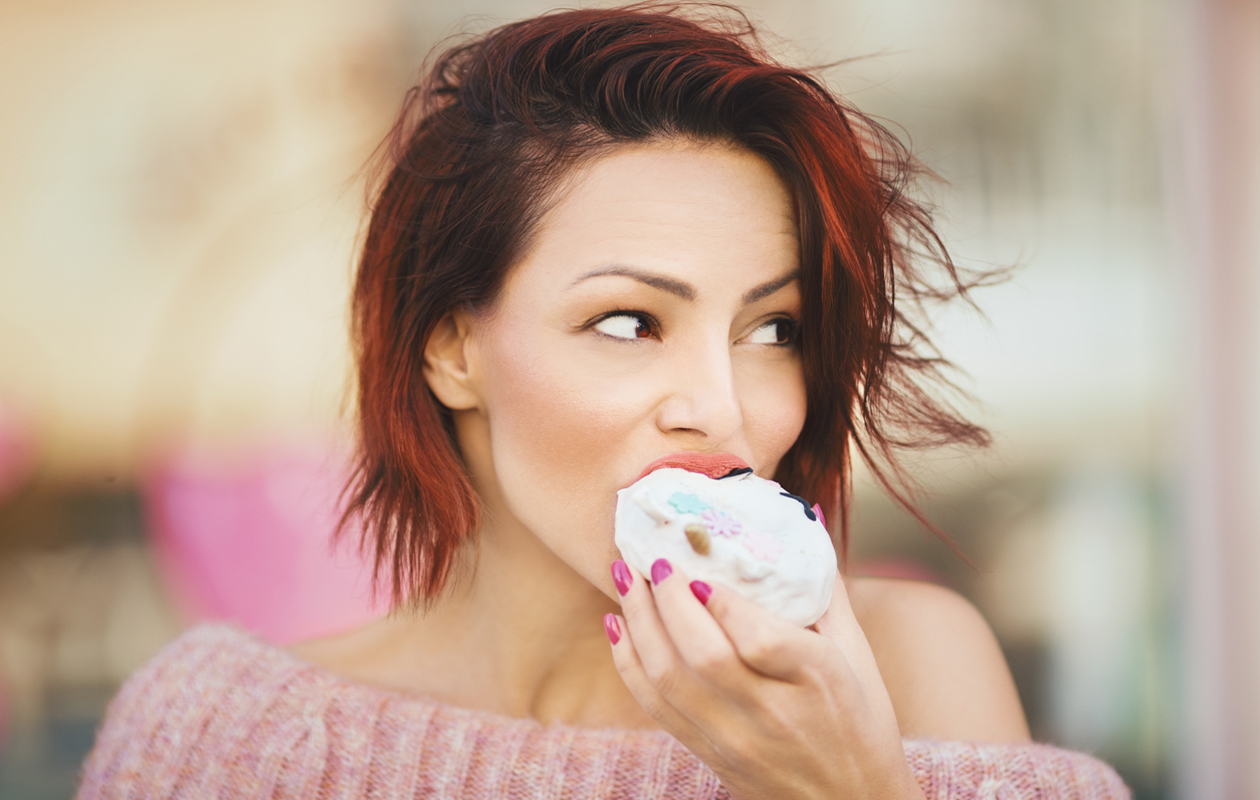 Nainen syö donitsia.