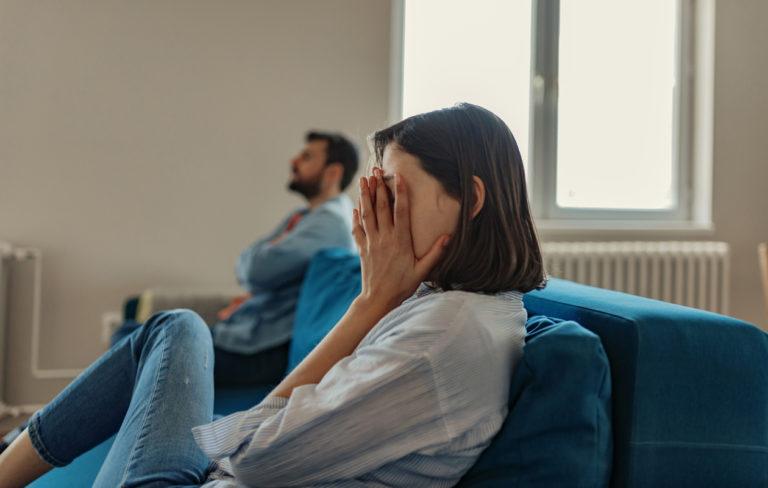 Nainen ja mies istuvat eri puolilla sohvaa.