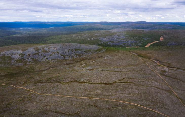 Mönkijäpolut viivoittavat tunturimaisemaa. Maisemasta vaaleana erottuu kuvassa oikealla sijaitseva aktiivinen kaivausalue.
