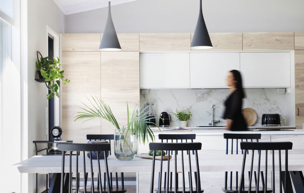 Koti on vaalea olematta valkoinen. Puupinnat tuovat kodikkuutta valkoiseen keittiöön. Ruokailutilan pöytä sointuu sävyltään keittiön oviin. Pöytä ja tuolit Vekestä. Bora-liesituuletin ja Dekton Entzo -tasot Omega-keittiöiltä. Kattovalaisimet Innolux. Pintamateriaalitoimittaja on Värisilmä Oulainen, parkettilattia Parla Tammi Chalet Tundra.