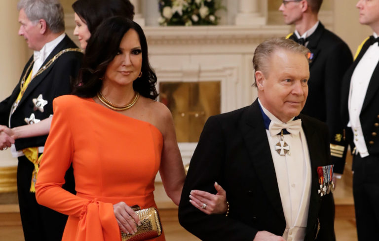 Elina Kanerva saapui Linnan juhliin kirkkaan oranssissa, pitkässä mekossa, jonka toinen hiha on pitkä ja toinen hihaton.