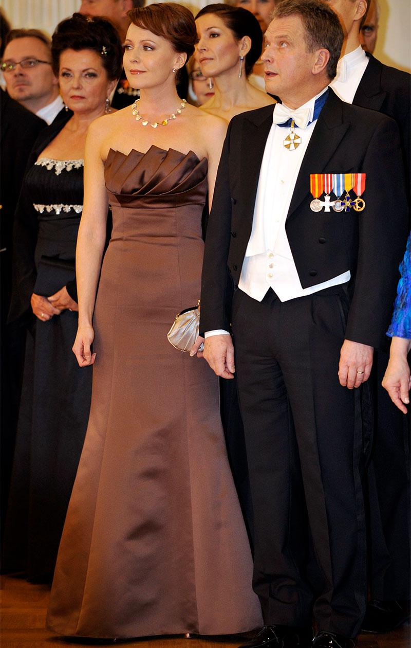 Jenni Haukio ruskeassa iltapuvussa vieressään Sauli Niinistö. Kuva: Lehtikuva