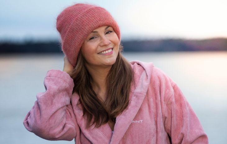 Janina Fry vaaleanpunaisessa kylpytakissa uimarannalla.