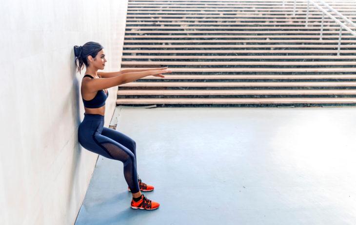 Kehonhuolto-ohjelma: kehonhuolto kotona. Nainen nojaa seinään ja tekee kyykkyä.