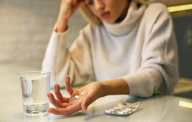 Nainen pitelee särkylääkkeitä käsissään.