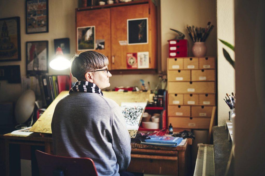 Sarjakuvataiteilija Tiitu Takalo työhuoneellaan. Hän piirtää ja värittää piirroksensa käsin paperille. Tietokonetta hän käyttää vain harvoin.