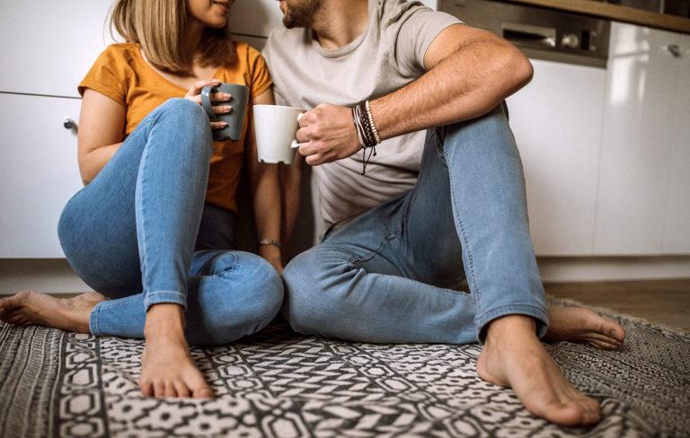 Pari istuu lattialla ja keskustelee.