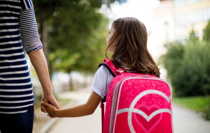 Äiti ja tytär menossa kouluun. Koulukiusaamisen jäljet saattavat aktivoitua jälleen, kun oma lapsi menee kouluun.