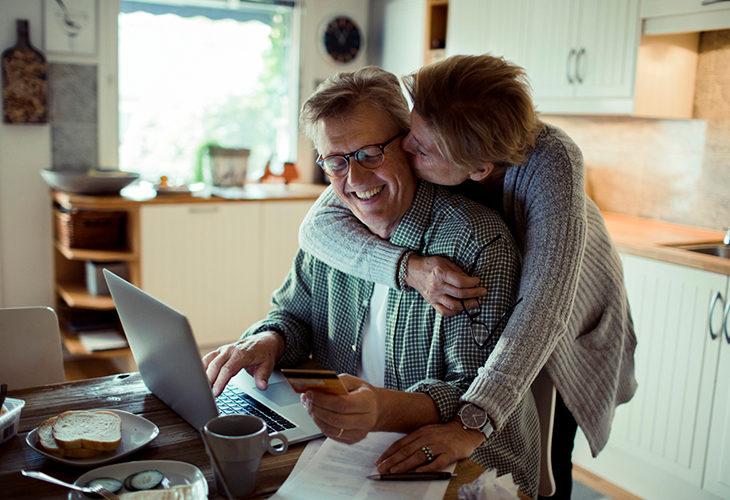Nainen on kumartunut halaamaan keittiössä istuvaa miestään.