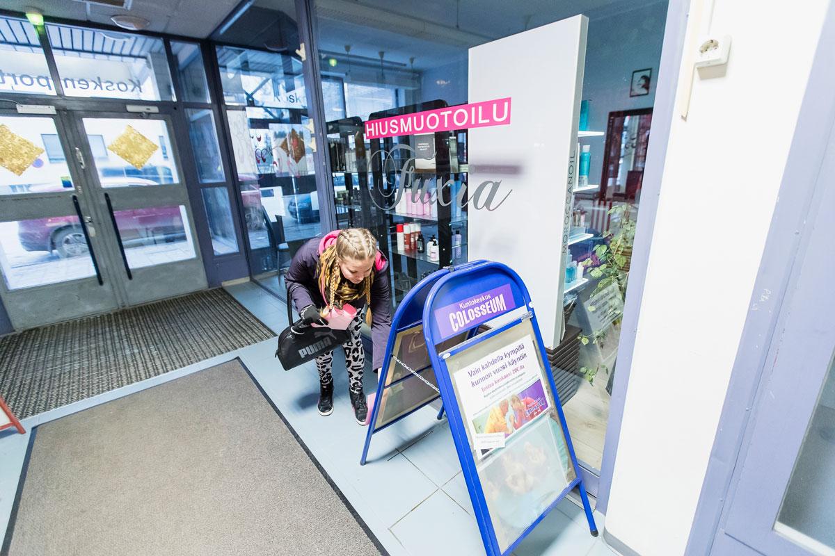 Janni poistaa vanhoja mainoksia kuntosalin standista.