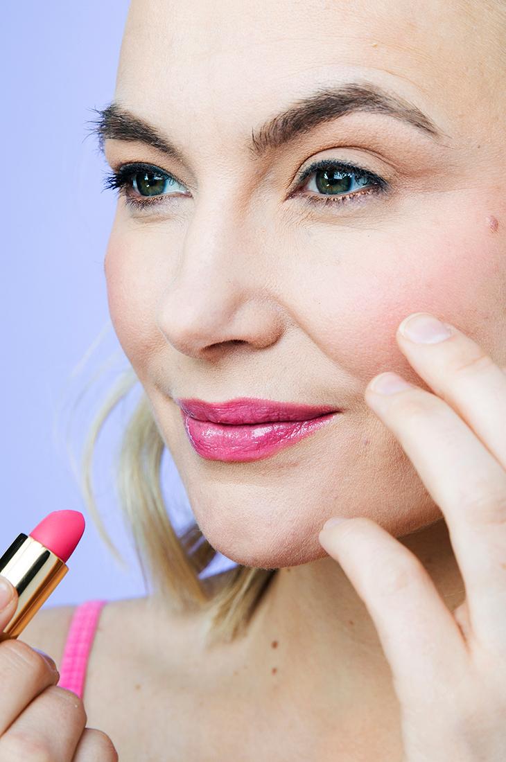 Nainen poseeraa kameralle huulipuna kädessä ja näyttää meikkitutoriaalissa, kuinka kevään trendimeikki tehdään.