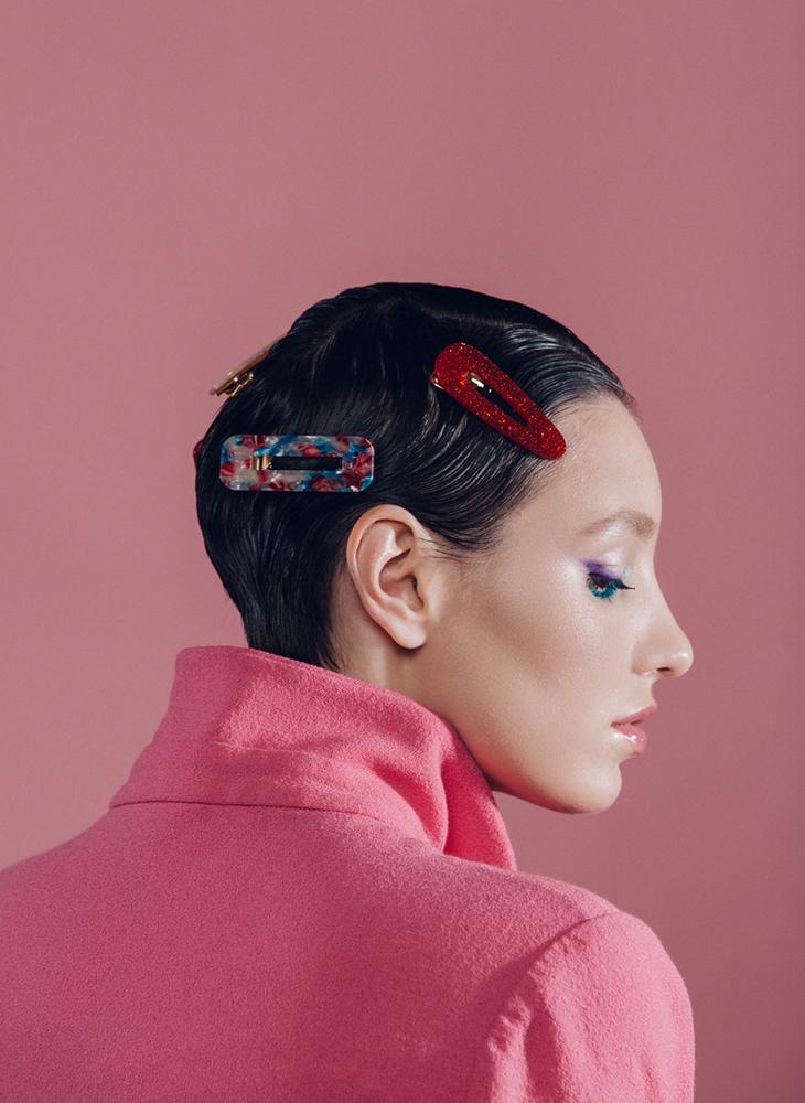 Lyhyet hiukset leikannut nainen poseeraa kuvassa hiuspinnit tukassaan.