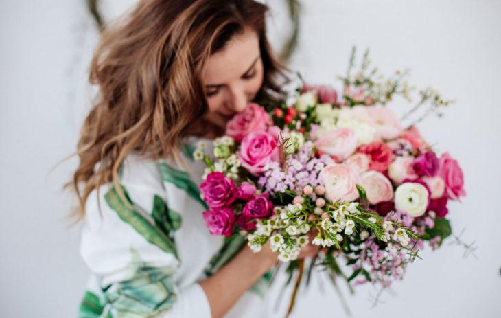Nainen tuoksuttaa sylissä olevia kukkia.