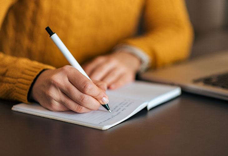 Nainen kirjoittaa muistivihkoon. Työmuisti vaatii tyhjentämistä, jotta vältyttäsiin työmuistin ylikuormittumiselta.