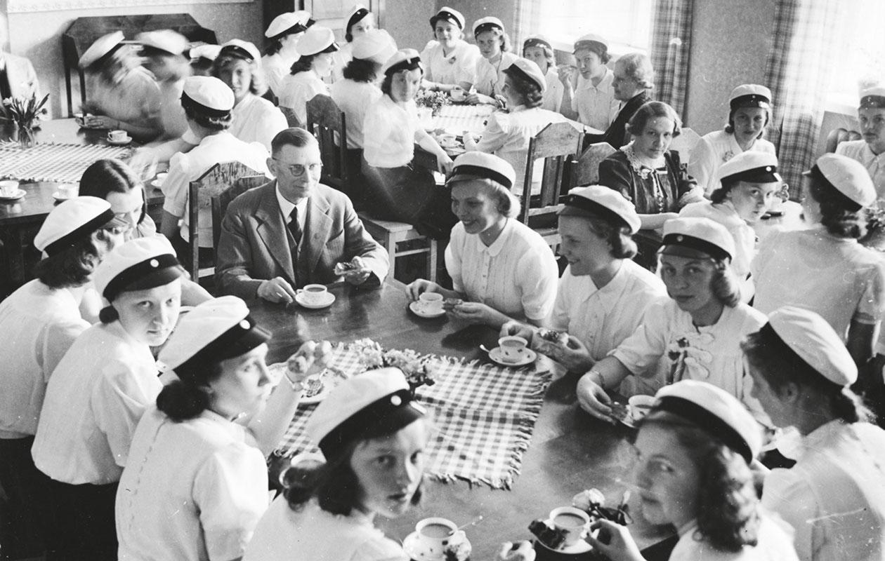Mustavalkoinen kuva ylioppilaista pöydän ympärillä.