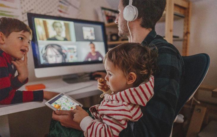 Etätyötä tietokoneella tekevä isä lastensa kanssa. Koronahokemat, kuten digiloikka, ovat tulleet tutuksi koronaviruspandemian aikana.