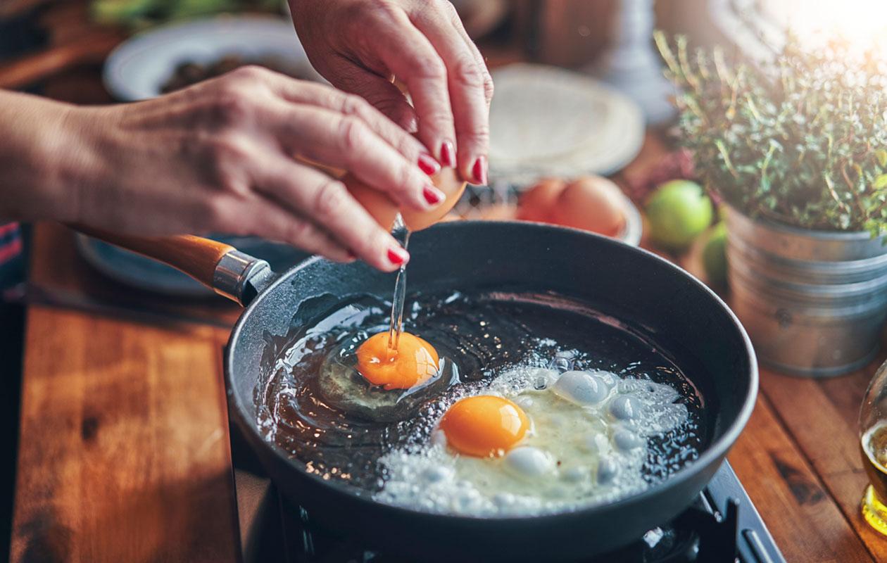 Nainen paistaa kananmunia valurautapannussa.