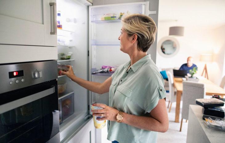 Nainen seisoo jääkaappipakastimen edessä. Tuottee, joissa on parasta ennen -päivämäärä on syytä säilyttää oikein, etenkin, jos ne aikoo pakastaa.