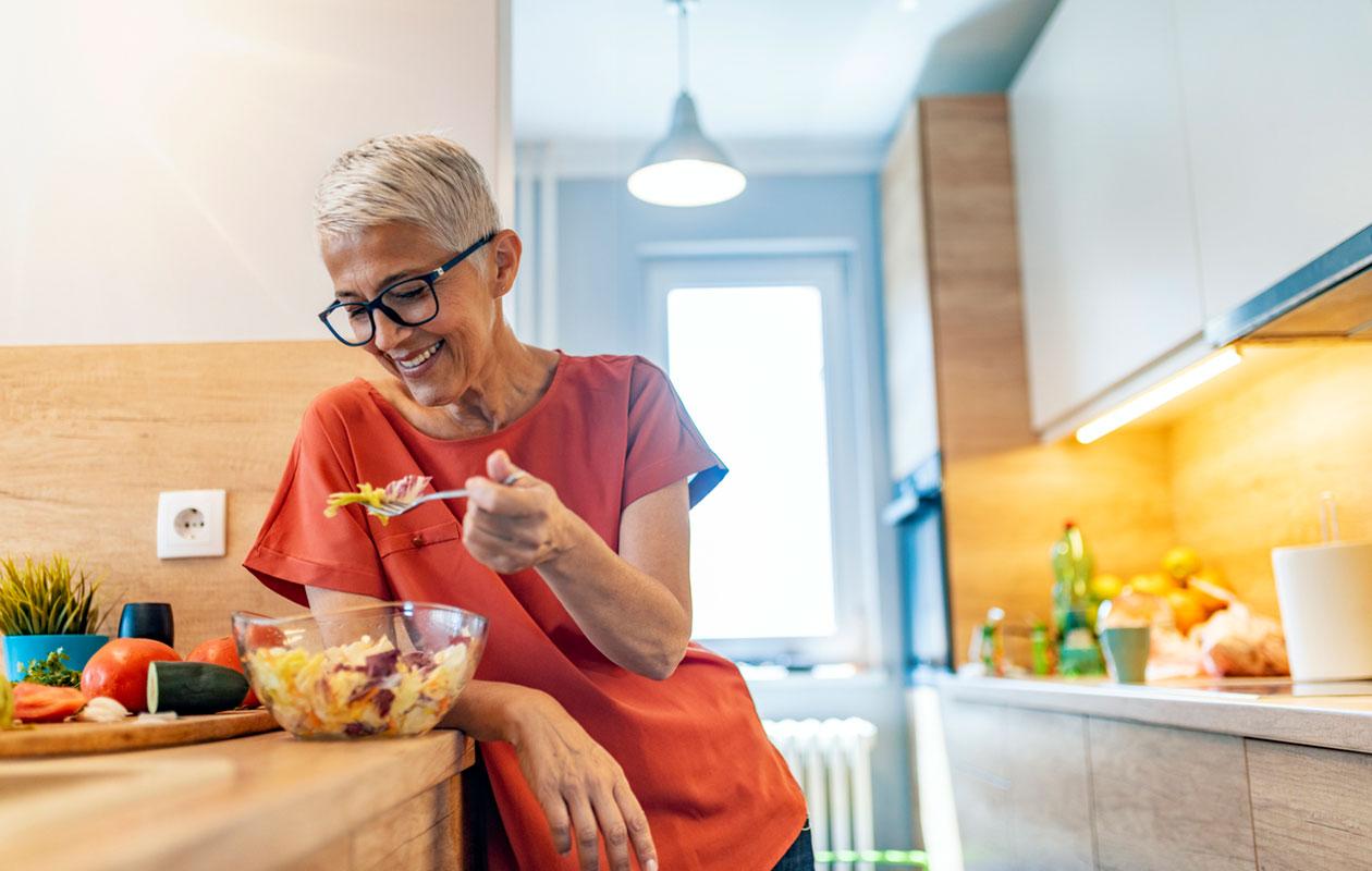 Nainen seisoo keittiössä syömässä salaattia.