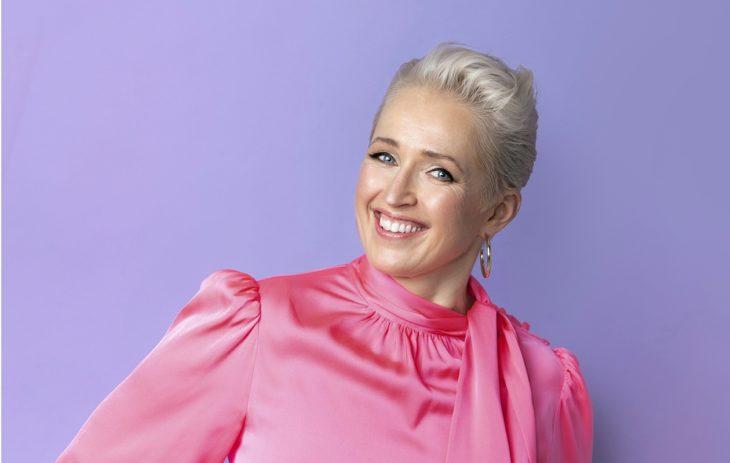 Anna Perho hymyilee kuvassa vaaleanpunaisessa paidassa.