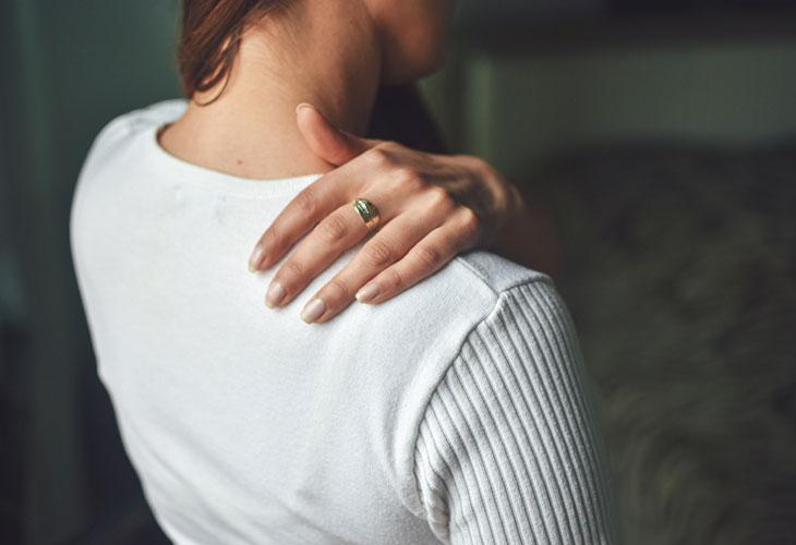 Nainen pitelee hartiaansa. Jäykät nivelet ja lihakset voivat johtua monesta eri syystä.
