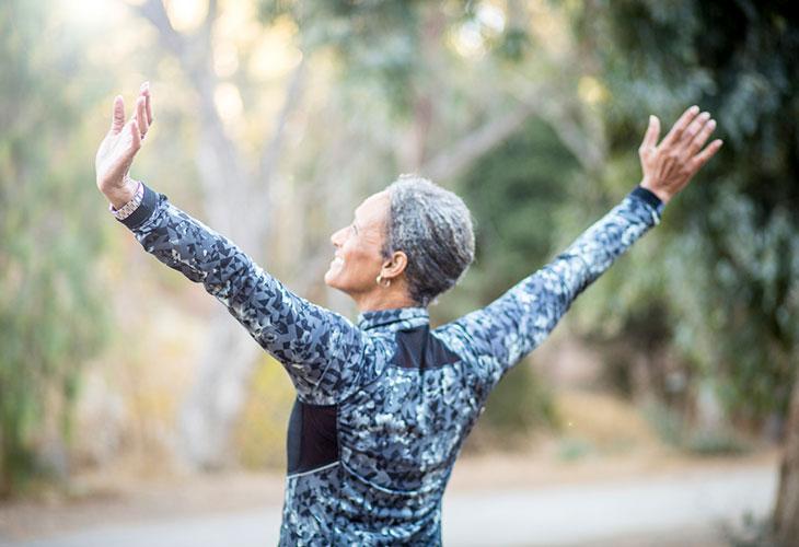 Nainen venyttelee metsässä kädet ilmassa. Jäykät nivelet tarvitsevat liikettä.