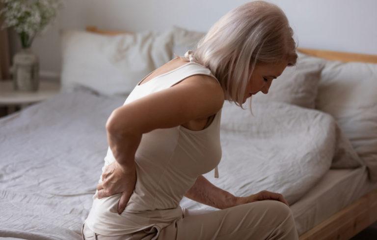 Nainen istuu sängyllä ja pitelee alaselkäänsä.