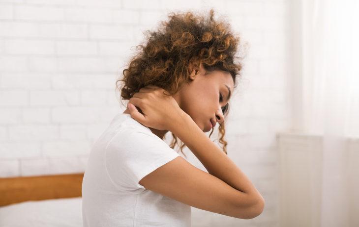 Ahdistunut nainen, joka kärsii niska-hartiakivuista. Miltä ahdistus tuntuu fyysisesti? Psyokologin mukaan usein esimerkiksi niska- ja hartiaoireilta.