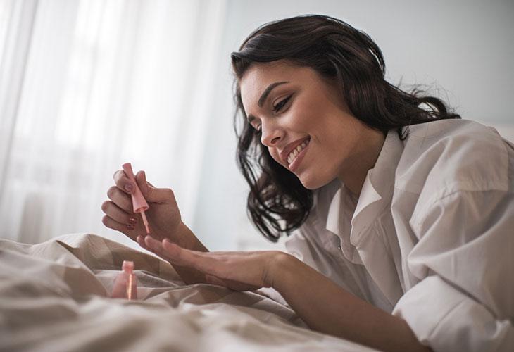 Nainen lakkaa kynsiään sängyllä. PItkät kynnet voivat olla epähygieeniset.