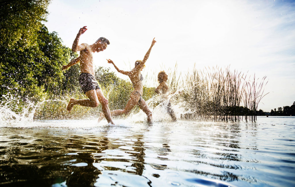 Kolme ihmistä ovat juoksemassa järveen juhannuksena.