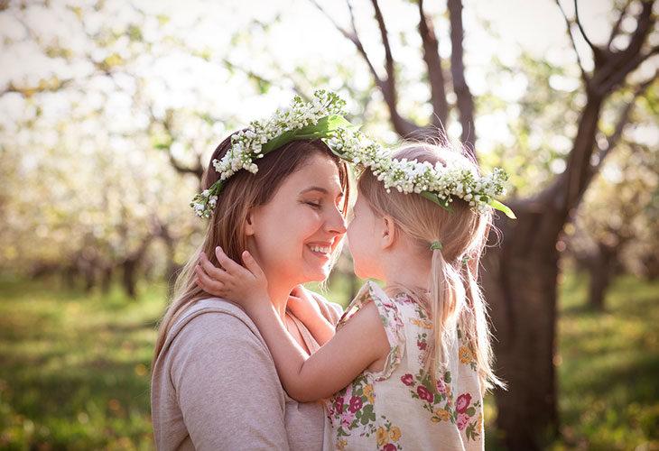 Äiti ja lapsi kuvassa kukkaseppeleet päässä.
