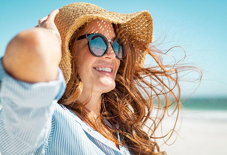 Nainen kesähatussa rannalla. Turvotuksen poisto ja muut vinkit helteelle.