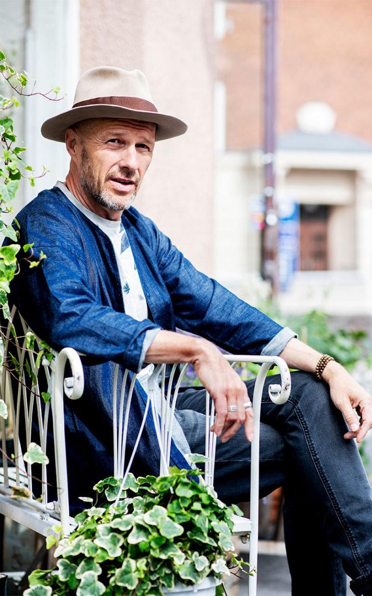 Kosketus on merkittävä voima. Jussu Pöyhönen istuu ulkona tuolilla. Muusikko Jussu Pöyhönen on kokenut keikoillaan yleisön henkisen kosketuksen.