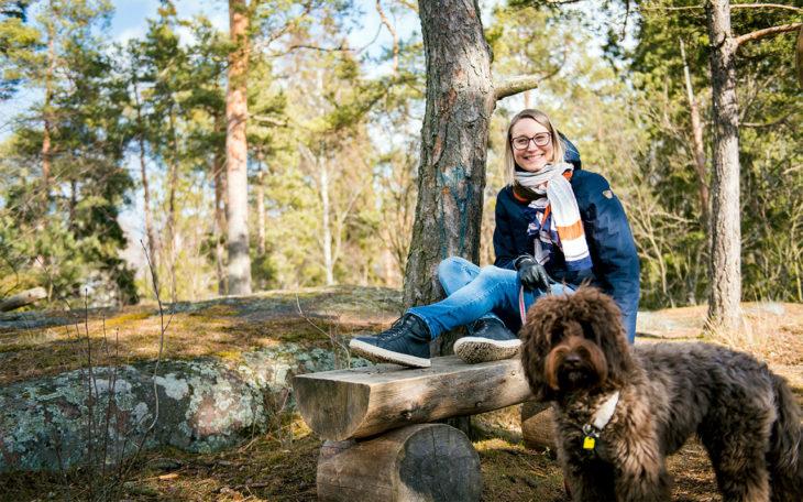 Teija istumassa koiransa kanssa metsässä.Jatkuva kipu on vaativa elämänkumppani.